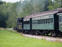 Steam Locomotive And Passenger Cars On Track. Steam Locomotive and passenger cars on travelling track through wooded area Stock Photos