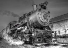 A Smoking steam locomotive prepares to depart. A steam locomotive on the tracks Stock Images