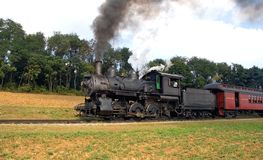 Steam locomotive and train. A view of a steam locomotive as it pulls a train along a track through the countryside in Strasbourg, Pennsylvania (USA royalty free stock photos