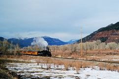 Steam Locomotive in The West. Steam Locomotive moving along the West with mountains in the background and snow in the foreground Stock Images