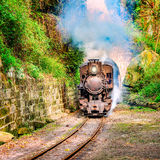 Steam narrow-gauge train. Steam narrow-gauge train moves from Yuejin to Bagou through the tunnel. Jiayang Mining Region. Sichuan province. China Royalty Free Stock Image