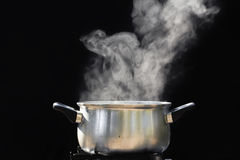 Steam over cooking pot. On dark background Stock Image