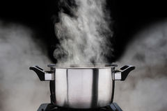 Steam over cooking pot. On dark background Royalty Free Stock Image