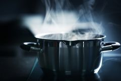 Steam over saucepan. In the dark royalty free stock photos