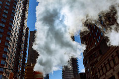 Steam pipe releasing hot air into the street in Midtown Manhattan. Stock Image