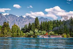 Steam-powered ship on lake Wakatipu surrounded by coniferous forest in Queenstown stock photography