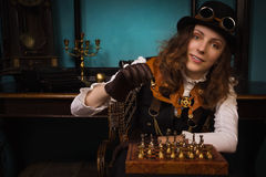 Steam punk girl plays chess Royalty Free Stock Image