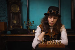 Steam punk girl plays chess Royalty Free Stock Photo