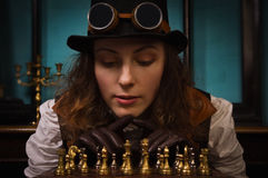 Steam punk girl plays chess Stock Photography