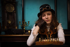 Steam punk girl plays chess Royalty Free Stock Images