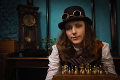 Steam punk girl plays chess Stock Photo