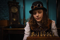 Steam punk girl plays chess Stock Images