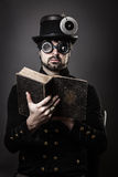 Steam punk man reading a book. Man in steam punk outfit reading a old book, wearing hat and sunglases Stock Photography