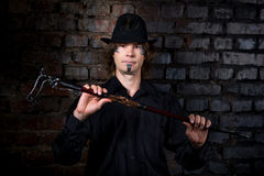 Steam punk man. Young handsome man boy model actor hostage slave captive. Art makeup paint black gray temple chin long hair. Hands chained desire call to action Stock Photography