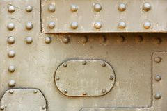 Steam punk metal background. Armored metal plates. Military steel bodywork, khaki armored vehicle, rivets, bolts, detail, army industry stock photos