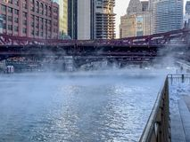 Steam rises from Chicago River as temperatures plunge on freezing January morning. While pedestrian braves weather on riverwalk stock image