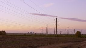 Steam rises from the cooling towers at power plant at dusk with electric power transmission lines in the foreground. Zoom out. Outdoors horizon landscape stock video