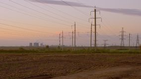 Steam rises from the cooling towers at power plant at dusk with electric power transmission lines in the foreground. Panning. Outdoors horizon landscape stock video