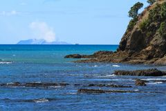 White Island, an active volcano, seen from the Whakatane Heads, New Zealand. Steam rises from the crater lake of White Island, a cone volcano located off the royalty free stock photo
