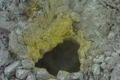 Steam rises from a hole in a yellow hard rock Sibolangit volcano Royalty Free Stock Images