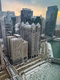 Steam rises from skyscrapers during frigid evening along a frozen Chicago River. Seen from up high stock images