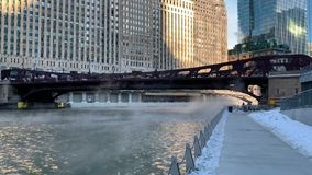Steam rising and blowing across the Chicago River as temperatures plunge on a freezing January morning in the Chicago Loop. Steam rising and blowing across the stock video