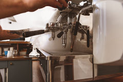Steam rising from the industrial coffee machine. Hands of a man using an espresso machine to make some beverage, side view stock images