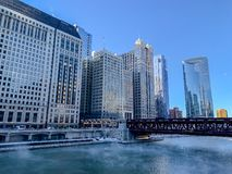 Steam risinmg from Chicago River as temperatures plunge on freezing January morning. With view of riverwalk, Wacker Drive, and moon setting stock photos