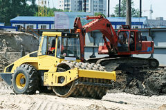 Steam roller and excavator on construction site. Road works Stock Photos