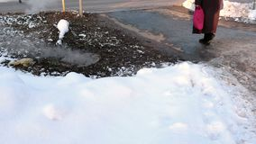 Steam is from sanitary sewer cover in snow, accident. Melted snow around. Snow drifts near