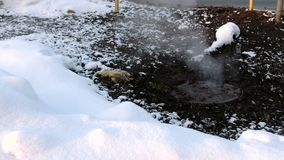 Steam is from sanitary sewer cover in snow, accident. Melted snow around.