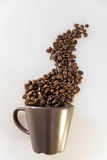 Steam shaped coffee beans and mug. Close up of coffee beans in shape of steam coming out of a brown mug stock photography