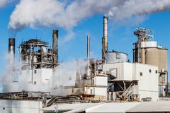 Steam and smoke emitting from an industrial factory smokestack I Stock Images