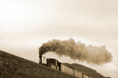 Steam train. Sepia tinted steam train travelling diagonally across the image Stock Photos