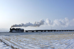 Steam train. Winter in the fields of running a steam train Royalty Free Stock Photo