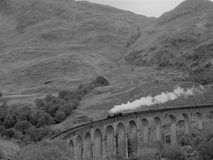 A steam train on an arch bridge, black and white stock photography