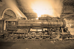 Steam train arrives to the station at night time. Royalty Free Stock Photos