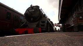 Steam train arriving at station A stock footage