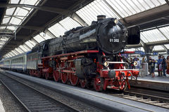 Steam train awaiting departure. Zurich, Switzerland - June 4, 2011: A train with a refurbished Pacific 01 202 steam locomotive is ready to depart from Zurich Royalty Free Stock Photo