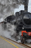 Steam train. Classic train leaving the station Royalty Free Stock Images