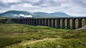A Steam train crosses a viaduct in Yorkshire. The Fellsman steam train crossing Ribblehead viaduct in Ribblehead, Yorkshire Royalty Free Stock Image