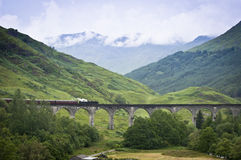 Steam train crossing an old viaduct Stock Photos