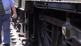 Steam train driver walks past camera with sound 4K stock video footage