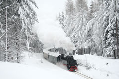 Steam train driving through snowy woods Stock Images