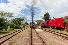 Steam Train Exhausts Station. Steam train locomotive with passenger coaches pulls out of countryside station with smoke exhaust fumes royalty free stock photography