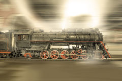 Steam train goes fast on the night station background. Stock Photo