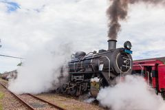 Steam Train Locomotive Closeup Exhausts. Steam train locomotive and coaches closeup exhausts pulls out of countryside station with smoke exhaust fumes stock photography