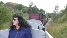 Steam train passenger enjoying a ride. Dark curly hair woman wearing glasses shows thumbs up sign enjoying steam engine train open air wagon bumpy ride in mining stock video