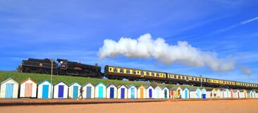Steam train passing colorful beach huts
