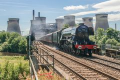Steam train passing a power station Stock Images